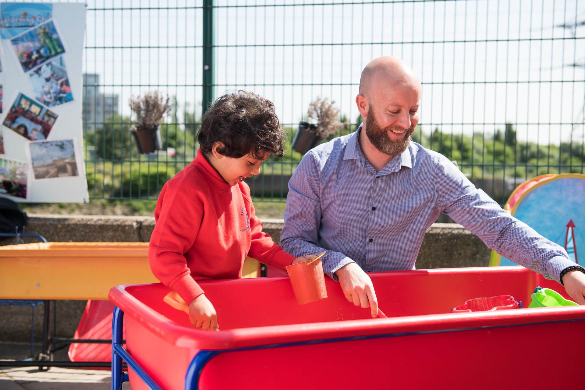 sand play eyfs setting male teacher and child